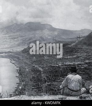 Man on Orange Hill looks over the dead city of St. Pierre, and up to steaming volcano, Mont Pelee. A pyroclastic - Stock Photo