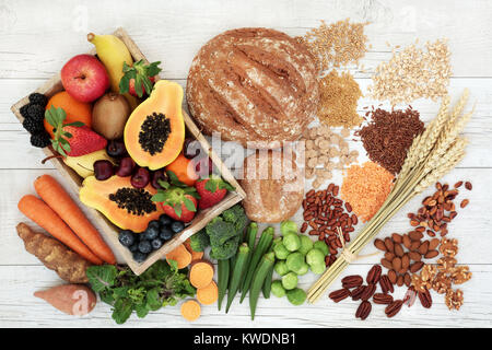 Healthy high fiber diet food concept with legumes, fruit, vegetables, wholegrain bread, cereals, grains, nuts and - Stock Photo