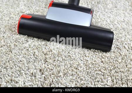 Vacuum cleaner dust brush on grey shaggy carpet surface - Stock Photo