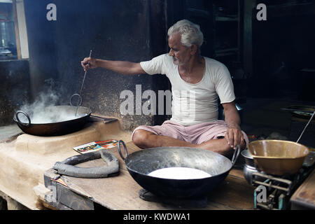 Street scene in Pushkar, Senior indian man sitting crossed legged on the floor of his workshop whilst cooking in - Stock Photo