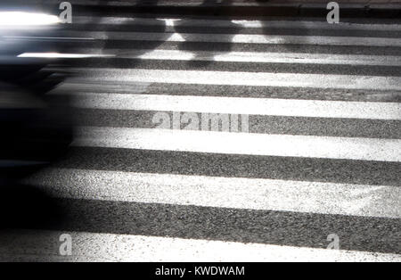Defocused shadows of pedestrians waiting to cross the street on zebra crosswalk and driving car ,  in black and - Stock Photo