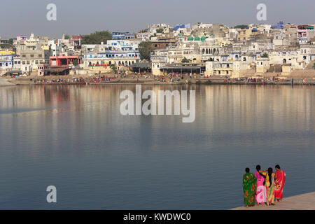 Four indian women in sari standing on the banks of holy lake at Pushkar with Hindu pilgrims taking ritual bath on - Stock Photo