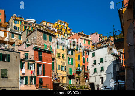 The colorful stacked homes and apartments in Riomaggiore Italy on the Ligurian coast at Cinque Terre - Stock Photo