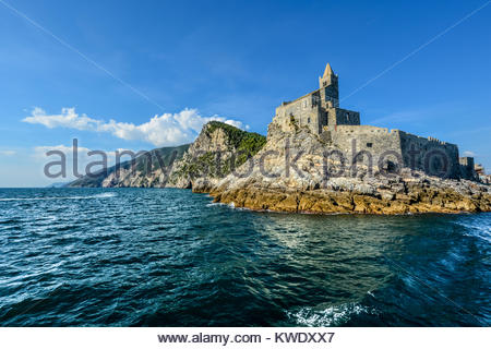 The imposing Church of St. Peter and the Doria Castle on the rocky peninsula at the entrance to Porto Venere Italy - Stock Photo