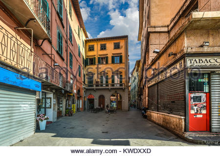 A very small sidewalk cafe opens for business alongside a narrow street in Pisa Italy - Stock Photo