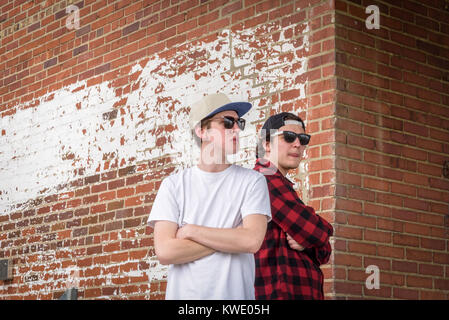 two young men wearing sunglasses and hats standing back to back with arms crossed against rustic brick wall in city - Stock Photo