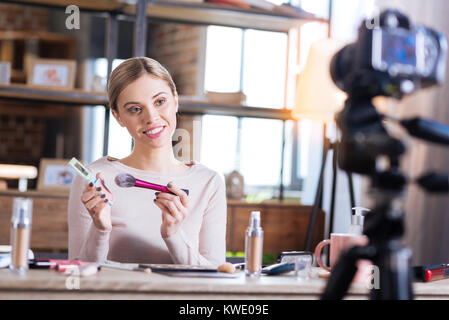 Cheerful attractive woman having a beauty blog - Stock Photo