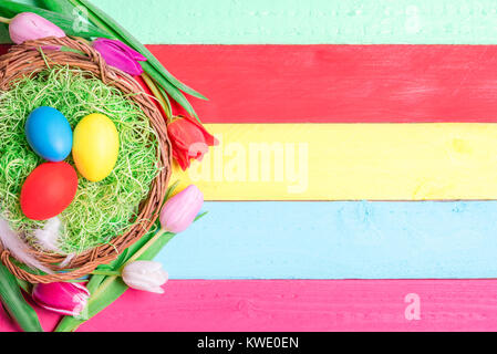 Easter banner concept with a wicker basket filled with decorative grass and painted eggs, surrounded by tulips, - Stock Photo