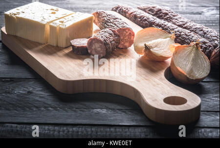 Tasty meal with homemade smoked sausages from beef and pork, fresh cheese and onion, displayed on a wooden cutting - Stock Photo