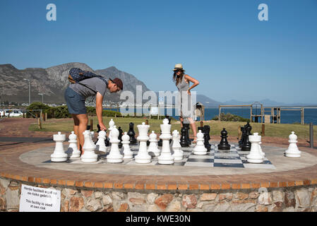 Hermanus Western Cape South Africa. December 2017. Couple playing an outdoor chess game on the seafront. - Stock Photo