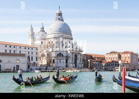 Gondolas with Asian tourists on the Grand Canal in front of Basilica di Santa Maria della Salute, Venice, Italy - Stock Photo