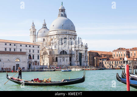 Gondolier  and gondola on the Grand Canal  in front of Basilica di Santa Maria della Salute, Venice, Italy in morning - Stock Photo