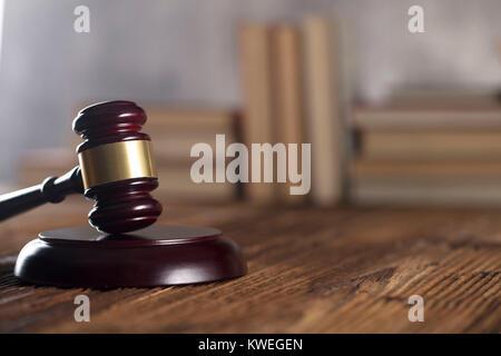 Gavel of judge on rustic wooden table. Bookshelf background.