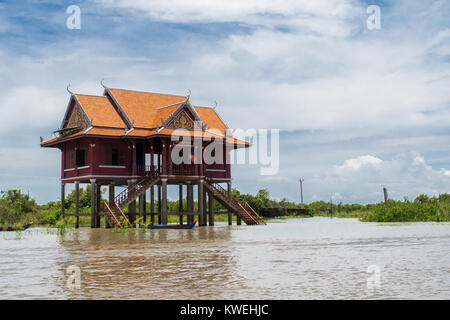 An orange and red building on stilts, floating, on the Tonle Sap river lake, in Kampong Phluk village, Siem Reap, - Stock Photo
