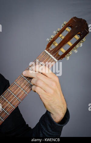 Guitarist playing an F major open chord on classical acoustic guitar ...