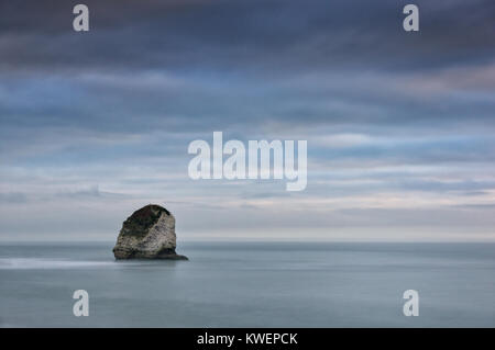 Gentle pastel sunset over isolated sea stack at Freshwater Bay, Isle of Wight - Stock Photo