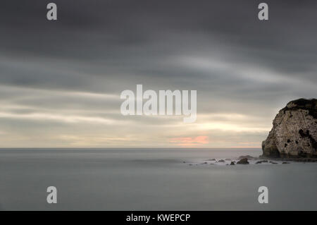Gentle pastel sunset over isolated cliff at Freshwater Bay, Isle of Wight - Stock Photo