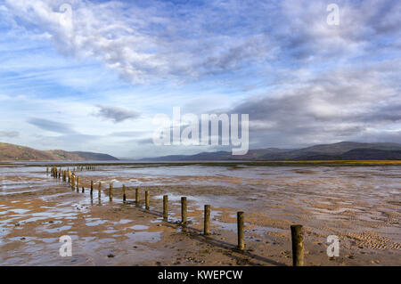 Sunny autumn light at Ynyslas nature reserve, Dovey Estuary, Wales at low tide, eroded fence in foreground and Cambrian - Stock Photo