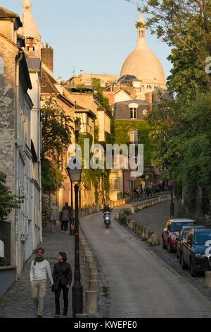France, Paris, Couple walking down street with Sacre Coeur, Montmartre