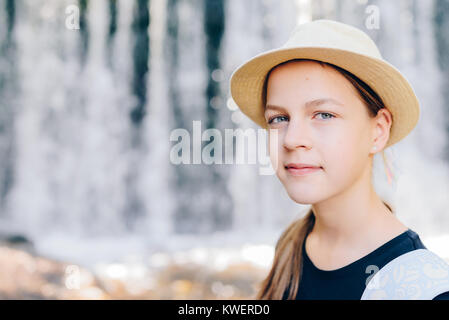 Pretty female girl tourist smiling in front of waterfall in  Polish Mountains. Beautiful young photographer takes - Stock Photo