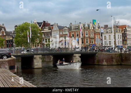 Amsterdam, Netherlands - July 30, 2011: Tourist boat in Amsterdam Canal - Stock Photo
