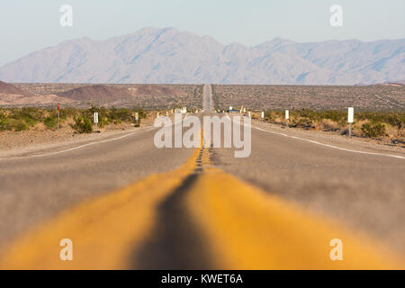 Classic horizontal panorama view of an endless straight road running through the barren scenery of the American - Stock Photo