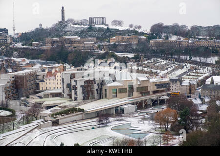 Snow falls on city of Edinburgh in December. Skyline view of city towards the Scottish Parliament Building at Holyrood - Stock Photo