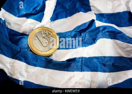 Eurocoin on crumpled Greece flag, symbolic photo debt quarrel, Euromünze auf zerknitterter Griechenlandfahne, Symbolfoto - Stock Photo