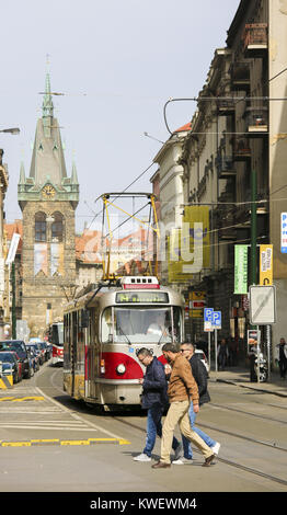 Red tram and unidentified people in the historic center of Prague, Czech Republic, with the Jindrisska Tower in - Stock Photo