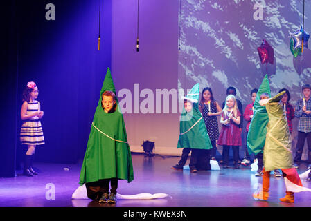 Children dressed as pine trees during their christmas show - Stock Photo