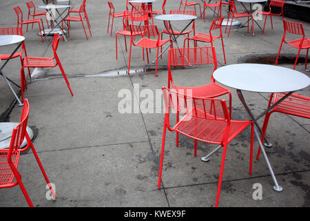 Empty sidewalk cafe with red chairs - Stock Photo