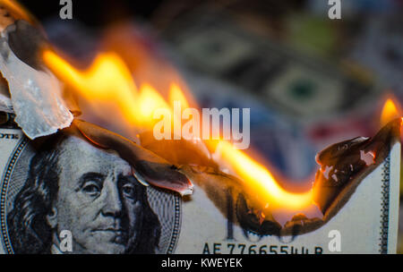 A hundred dollar bill in American US currency is on fire - Stock Photo