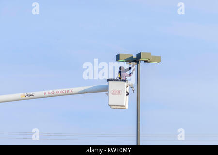 A workman in a lift bucket works on a shopping mall light fixture. Oklahoma City, Oklahoma, USA. - Stock Photo