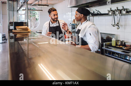 Two male cooks wearing uniform working in commercial kitchen. Professional chefs discussing the taste of new dish - Stock Photo