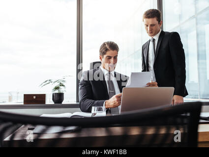Business partners working together looking at contract papers. Two corporate professionals in office going through - Stock Photo