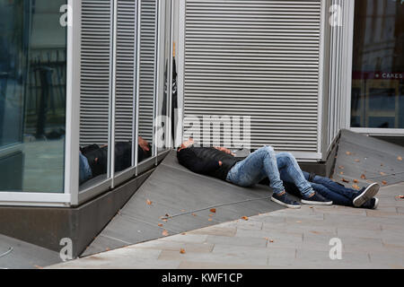 Two homeless men pictured sleeping outside a Pret Cafe in London, UK. - Stock Photo