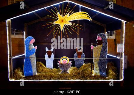 Bright stylized nativity set with comet star in a town square - Stock Photo