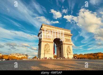 Arc de Triumph in Paris with beautiful clouds behind on a bright afternoon in Autumn. Panoramic filtered mage. - Stock Photo