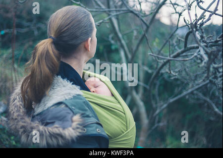 A young mother with her baby in a sling is walking in nature - Stock Photo