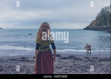 A young woman is walking her dog on the beach - Stock Photo