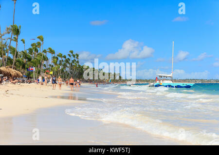 Punta Cana, Dominican Republic - December, 2017: tourists relaxing on sunny beach - Stock Photo