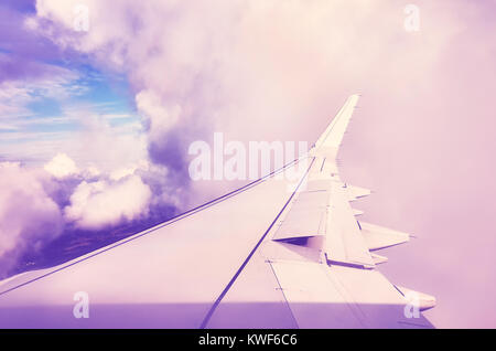 A plane wing in clouds seen through a window of an aircraft, color toned travel concept picture. - Stock Photo
