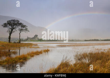 Kilchurn Castle, Loch Awe, Scotland on a rainy day in October with a rainbow appearing to emerge directly from the - Stock Photo