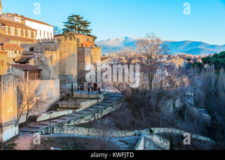 Walls of the city of Segovia buildings that surround it and in the background you can see the mountains of the Sierra - Stock Photo