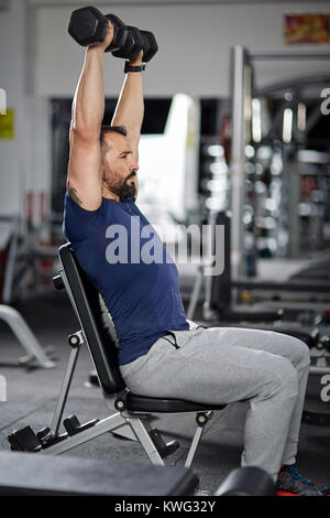 Man doing shoulder workout with dumbbells in the gym - Stock Photo