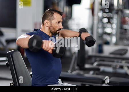 Man doing shoulder workout with dumbbells - Stock Photo