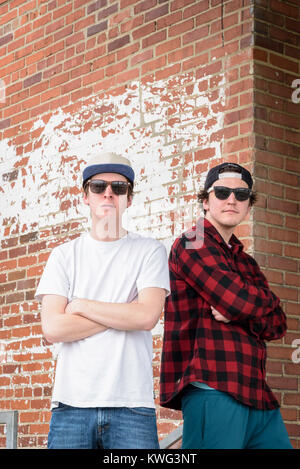 two young men wearing sunglasses and hats standing back to back with arms crossed against brick wall - Stock Photo