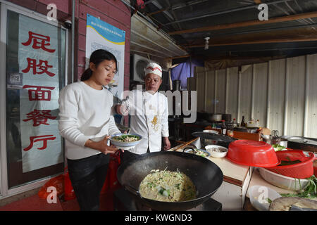 (180104) -- NAN'AN, Jan. 4, 2018 (Xinhua) -- Guo Weilan (L) works at the noodle shop in Pendao Village of Penghua - Stock Photo