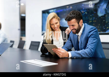 Attractive business couple using tablet in their company - Stock Photo