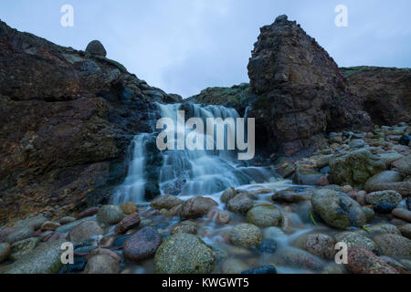 Waterfall onto the beach at Nanjizal Bay in West Cornwall - Stock Photo